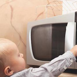 Enfant touchant un micro-ondes